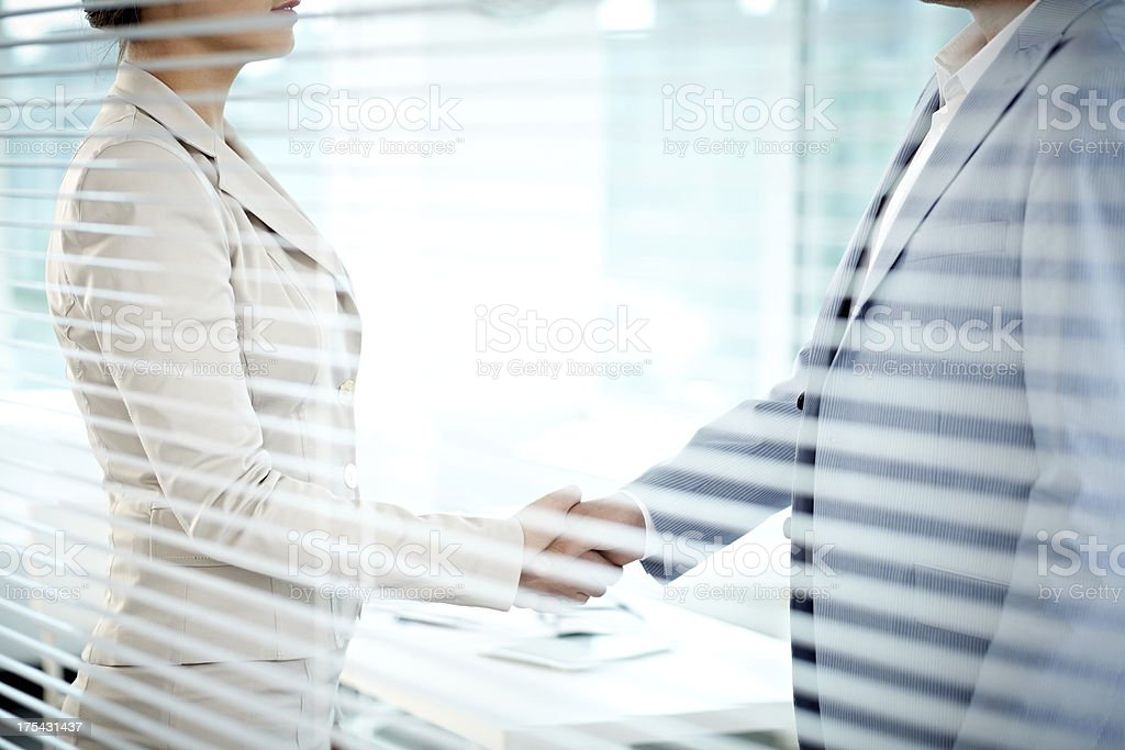 Handshake behind jalousie royalty-free stock photo