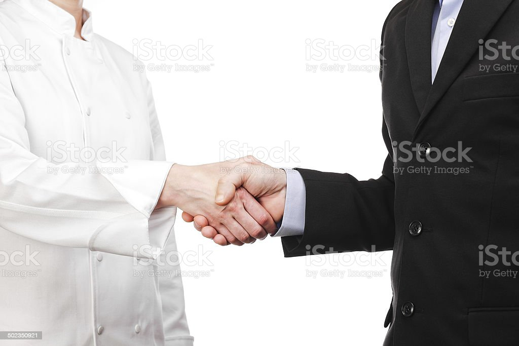handshake between a cook and a businessman stock photo