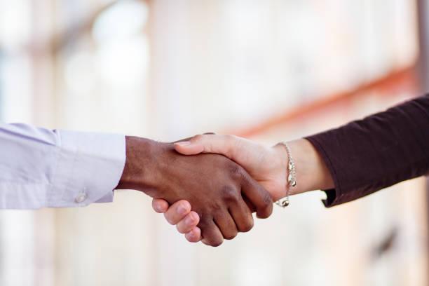 Handshake between african and a caucasian man. stock photo