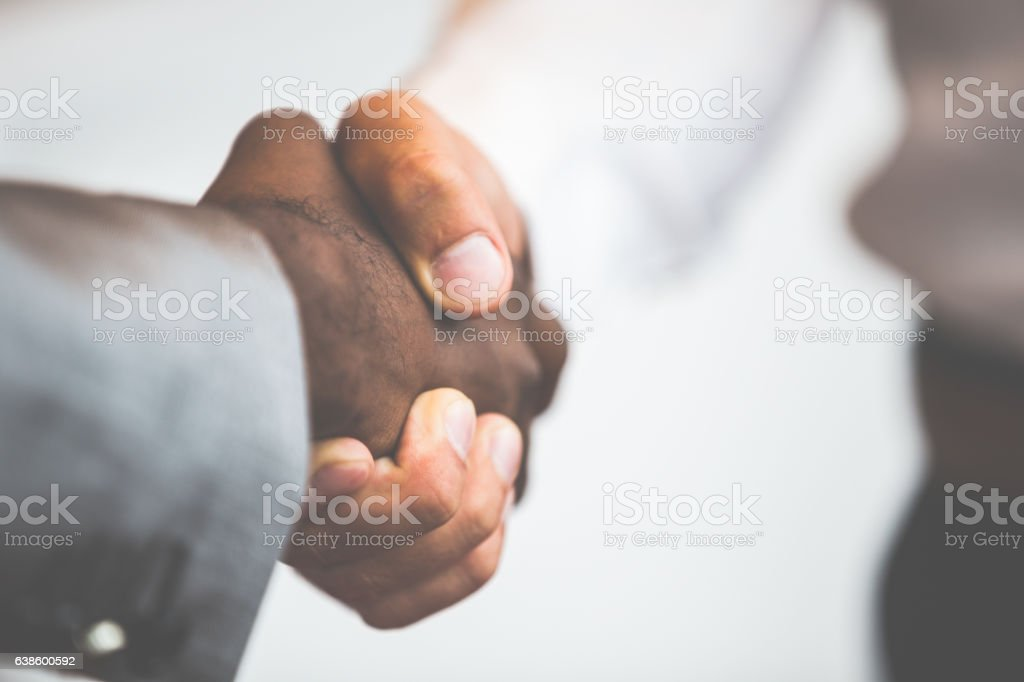Handshake between african and a caucasian man stock photo