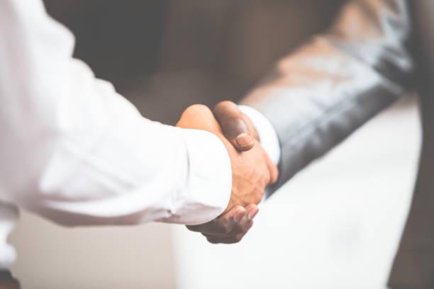 Handshake between african and a caucasian man stock photo