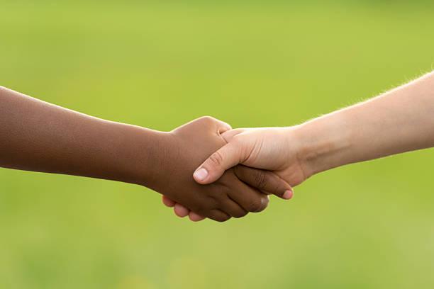 handshake between black and white boy - fond couleur uni photos et images de collection