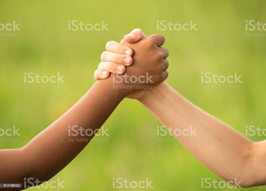 handshake between black and white boy stock photo