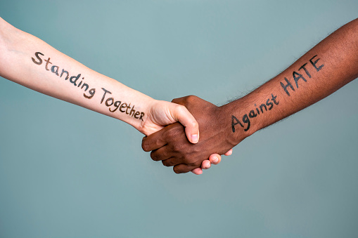 Handshake between black and white human woman and male hands with the message text Standing Together against HATE. Concept of protest protest against racism and police brutality.