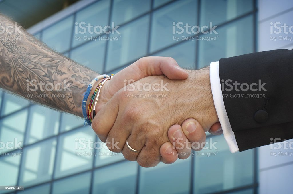 Handshake between businessman and tattooed bad boy royalty-free stock photo