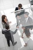 istock handshake business partners behind the glass door 1006900348