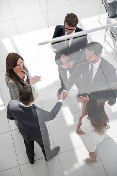 handshake business partners behind the glass door stock photo