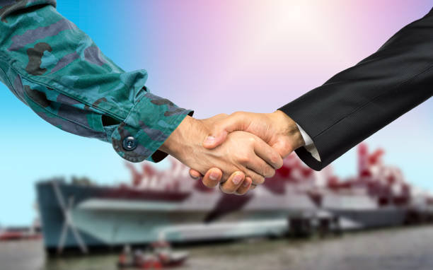 handshake business with the naval army American soldier in uniform and civil man in suit shaking hands with a USS Destroyer and Littoral Combat Ship naval base stock pictures, royalty-free photos & images
