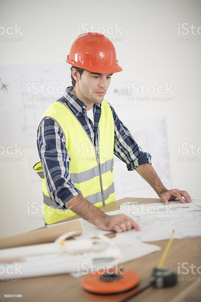 foreman in his office reviewing building plans