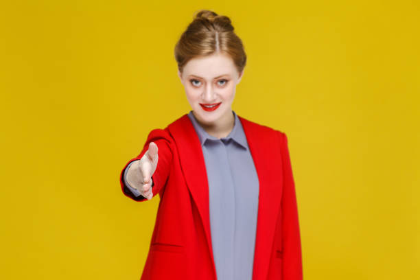 Handshake! Ginger red head business woman in red suit showing handshaking sign. - foto stock