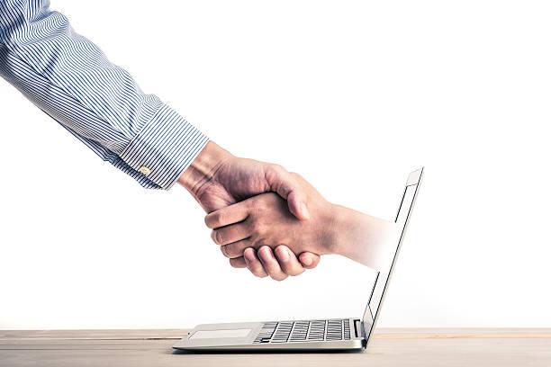 握手し、手の中のノートパソコンの画面 - リモート ストックフォトと画像