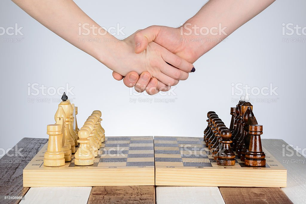 Handshake in front a game of chess stock photo