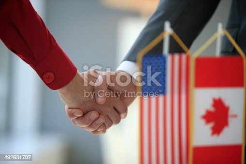 istock Handshake in front of usa and canada flags 492631707