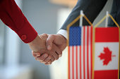 Usa and Canada flags, handshake in background, selective focus