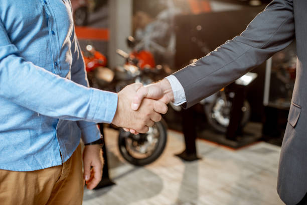 Handshake in the showroom with motorcycles stock photo