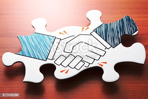 istock Handshake jigsaw puzzle pieces on wood desk. 912405390