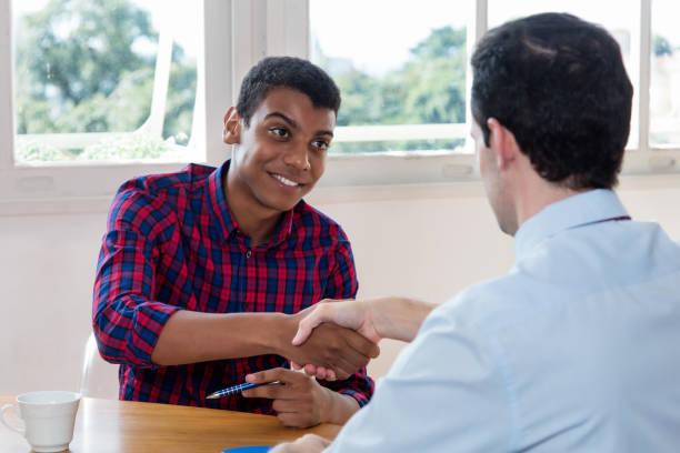 handslag för afroamerikanska manliga lärling efter anställningsintervju - job interview bildbanksfoton och bilder