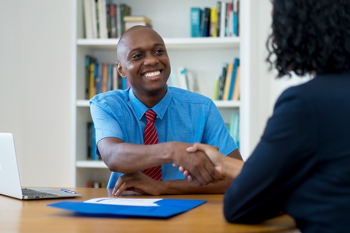 istock Handshake of african businessman and businesswoman after signing contract 1210046266