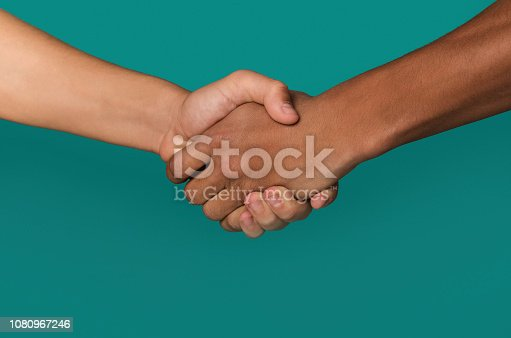 Handshake of afro-american and caucasian teenager hands, against blue background, closeup