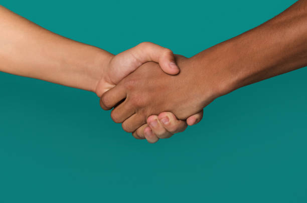 Handshake of afro-american and caucasian teenager hands stock photo