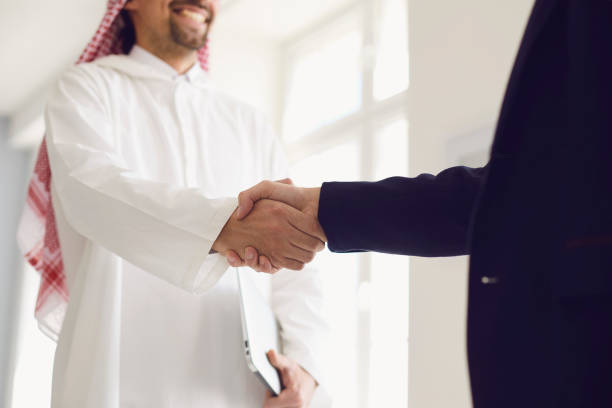 Handshake of arabic and european businesspeople in office. stock photo