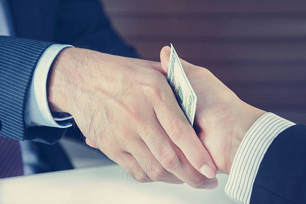 Handshake of businessmen with money, bribery concept - vintage tone stock photo