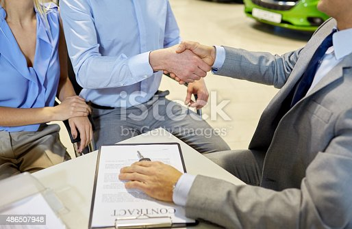 939005154 istock photo handshake of customer and car dealer in auto salon 486507948
