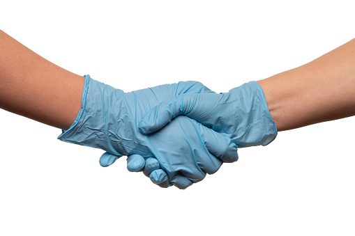 Handshake of gloved hands of doctors or people during covid-19 pandemic isolated on the white background