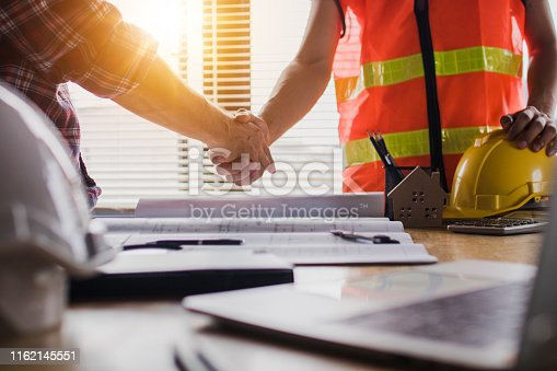 istock Handshake of two business man, after  architect working and planning blueprint, Engineering objects on workplace 1162145551