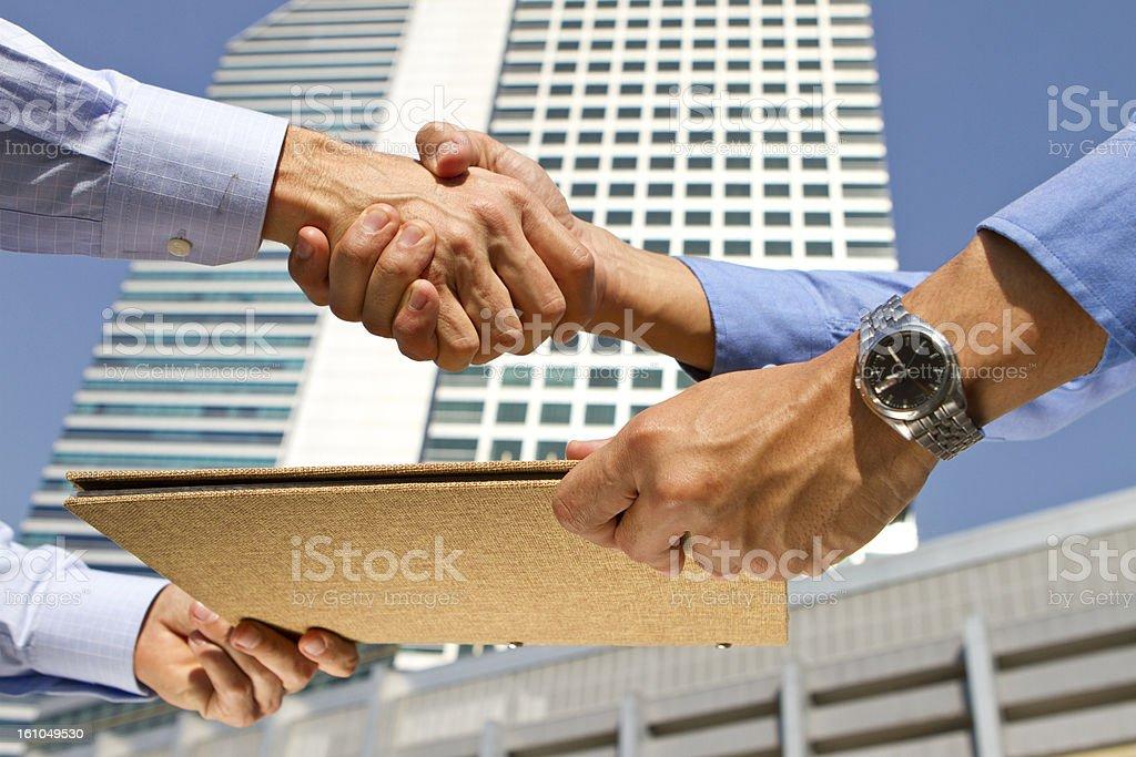 Handshake over a business agreement in a financial district royalty-free stock photo