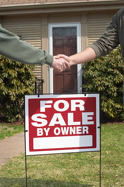 Handshake Over Home For Sale Sign stock photo