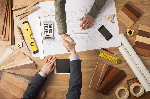 Architect and customer businessman shaking hands top view, desktop with building project, tools and wood swatches on background
