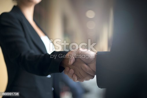 Two people shaking hands on business event.