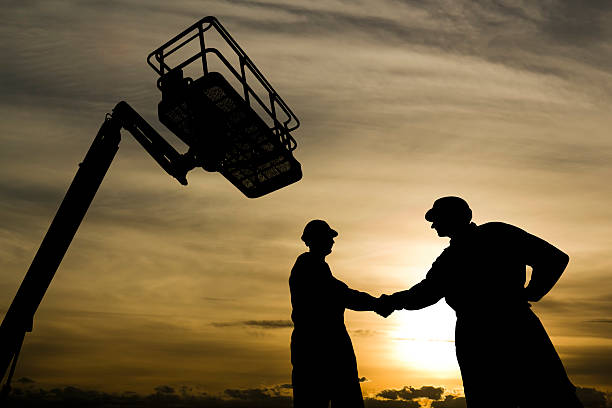 Handshake under a Lift A royalty free image from the construction industry of two construction workers shaking hands underneath a cherry picker. mobile crane stock pictures, royalty-free photos & images