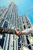 male and female businessperson handshakes and money falls from sky.