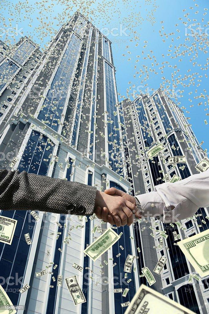 handshake under falling money stock photo