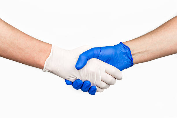 Handshake with blue and white medical gloves. stock photo