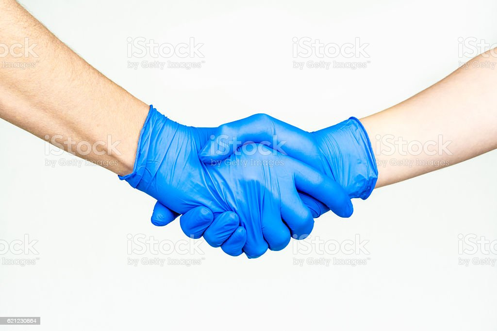 Handshake with blue medical gloves, stock photo