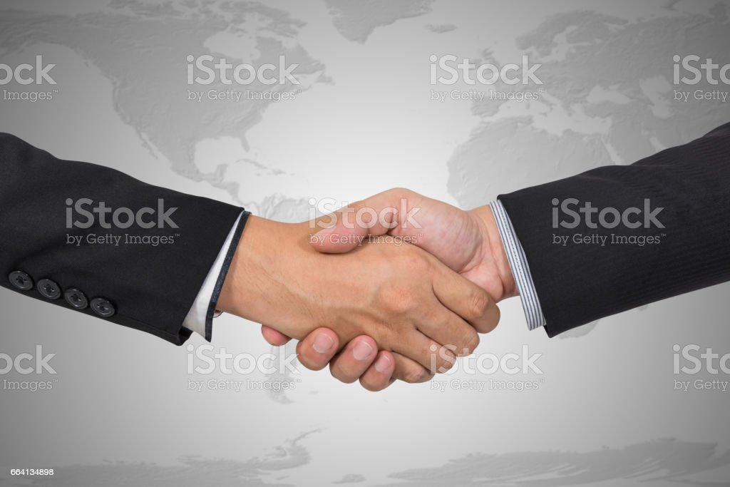 Handshake with map of the world in background, Elements of this image furnished by NASA foto stock royalty-free