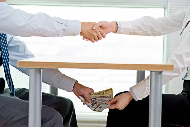 Handshaking and bribing stock photo