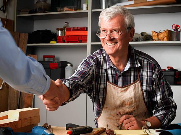 handshaking al workshop - pensionati lavoratori foto e immagini stock