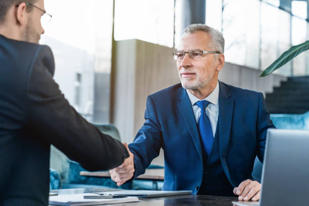 Handshaking between business partners after making a deal indoors Business, People, Formalwear, Indoor, Manager between stock pictures, royalty-free photos & images