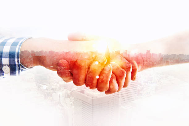 Handshaking business person in casual wear. concept of teamwork and partnership. double exposure - foto stock