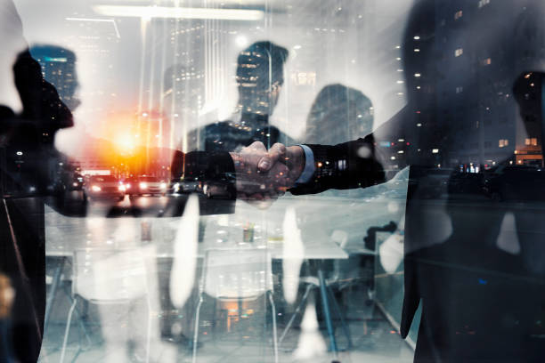 Handshaking business person in office. concept of teamwork and partnership. double exposure - foto stock