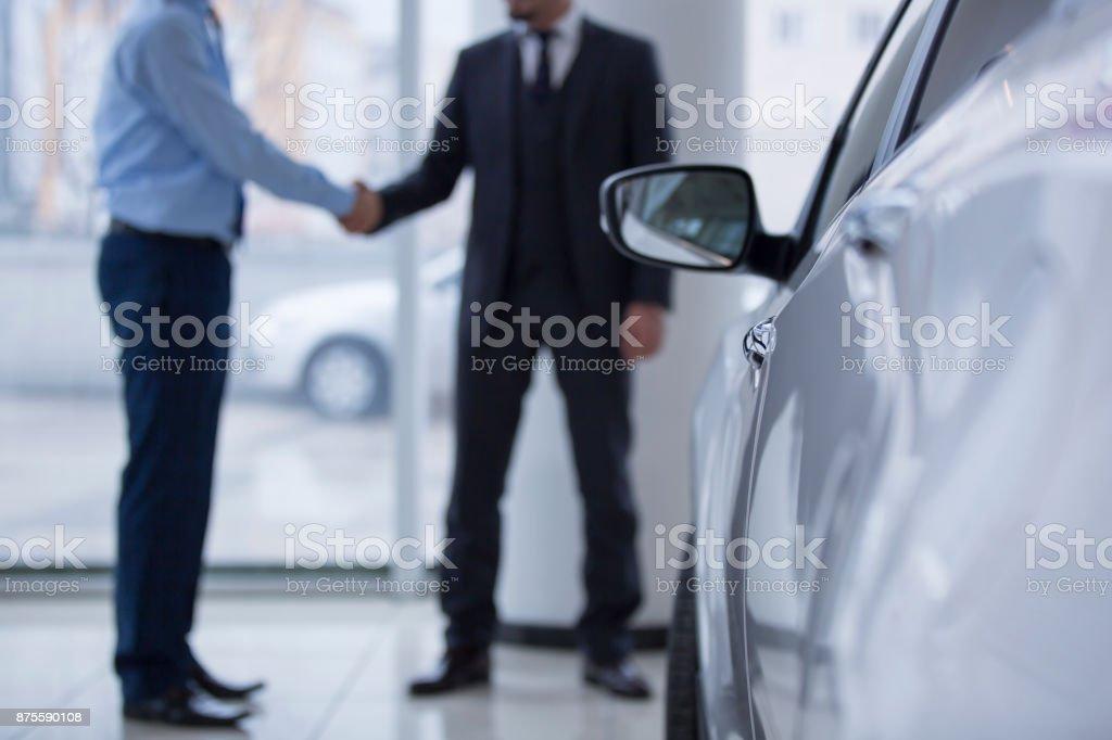 Handshaking in a car showroom stock photo