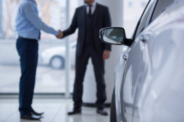 Handshaking in a car showroom Buying new car at car showroom car salesperson stock pictures, royalty-free photos & images