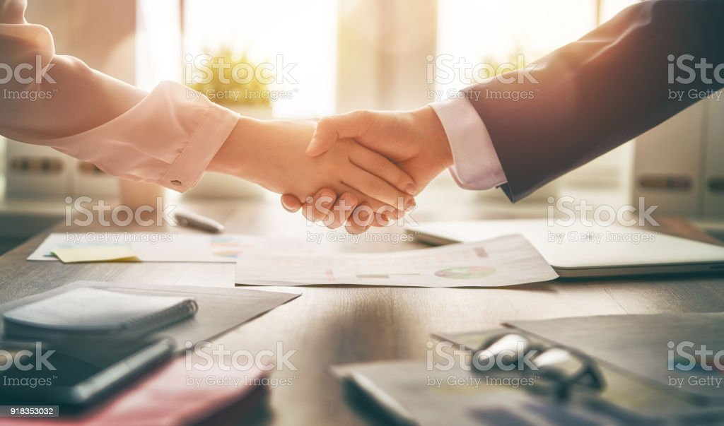 handshaking in office stock photo