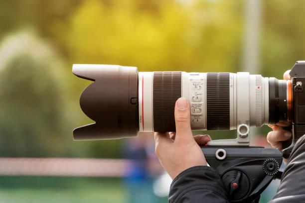 handshot van een professionele fotograaf buitenshuis. man houdt een moderne camera-apparaat. cameraman schiet buitenshuis. schieten met lens. paparazzi met high-end optische doelstelling. fotografische uitrusting - telelens stockfoto's en -beelden
