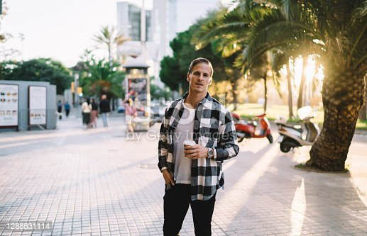 istock Handsome 20s male traveler in rendy wear standing on city square resting on evening holding coffee cup, pensive young hipster guy looking at camera visiting downtown on free time on weekends 1288831114