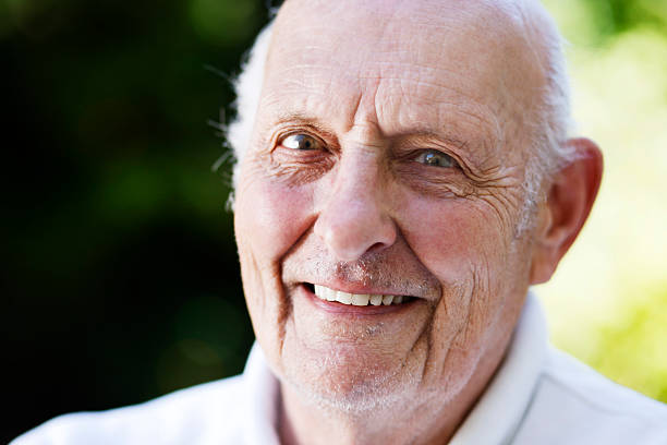 Handsome 80 year old man smiles at camera stock photo